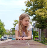 Cute girl lying on brick wall Stock Photos