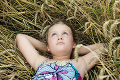 Cute girl lying in a field and dreaming Stock Photos