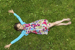 Cute  girl lying on the grass, arms outstretched, top view. Royalty Free Stock Image