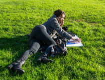 Cute girl lying on green grass and talking on the phone with notebooks Royalty Free Stock Photos