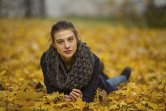 Cute girl lying on leaves in autumn Park. Happy. Stock Photo