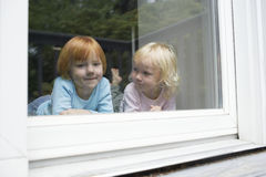 Cute Girl Lying With Sister In Front Of Glass Window Stock Image