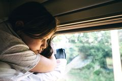 Cute girl lying on the top shelf in the train and looking out the window stock photo