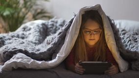 Cute girl lying under blanket with touch pad