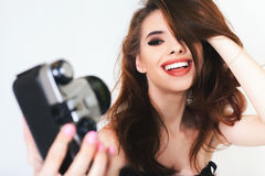 Cute girl make a foto selfie at vintage camera. Royalty Free Stock Images