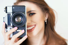 Cute girl make a foto selfie at vintage camera. Stock Photo