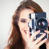 Cute girl make a foto selfie at vintage camera. Royalty Free Stock Photos