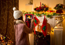 Cute girl making photo of decorated Christmas fireplace on digit Stock Images