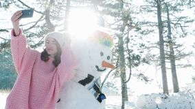 Cute girl making photo with a snowman, winter selfie, mobile phone in hand of a young woman making fun selfie photo in stock video