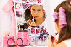 Cute girl making up her face with lipstick Royalty Free Stock Photos