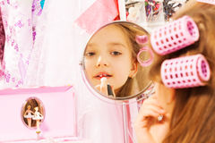 Cute girl making up her face looking in mirror Stock Images