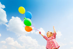 Cute girl with many balloons on sky background royalty free stock photography