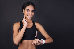 Cute girl measuring her pulse using smart watches. Control everything. Positive delighted woman looking straight at camera while counting her pulse standing Stock Photo