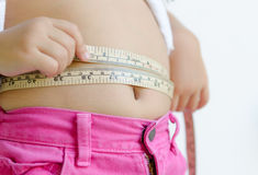 Cute girl measuring her stomach Stock Images