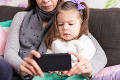 Cute Girl And Mom Watching Cartoon On Mobile Phone. Baby girl watching film on internet using smartphone while sitting with parent at home stock images