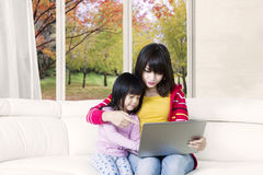 Cute girl and mother with laptop on couch Stock Images