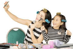 Cute girl and mother take pictures on studio Stock Images