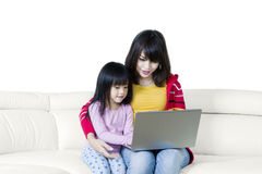 Cute girl and mother using laptop on couch Stock Photos