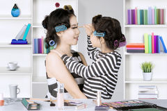 Cute girl and mother using mascara Royalty Free Stock Photography