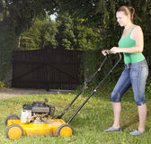 Cute girl moving the grass with yellow lawn mover stock images