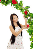 Cute girl near the arch entwined by roses Royalty Free Stock Image
