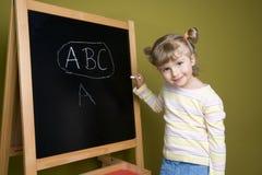 Cute girl near blackboard Royalty Free Stock Photos