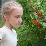 Cute girl near a currant bush Royalty Free Stock Photography