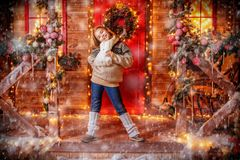 Cute girl near house. A full length shot of a pretty girl standing on the porch of a house decorated for Christmas and New Year. Merry Christmas, happy New Year royalty free stock images