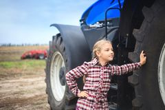 Cute girl near the modern tractor in the field royalty free stock photo