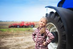 Cute girl near the modern tractor in the field stock photos