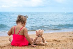 Cute girl near the sea. Young girl with teddy bear sitting on the beach. royalty free stock photos