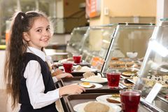 Cute girl near serving line with healthy food in canteen. Cute girl near serving line with healthy food in school canteen stock photo