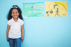 Cute girl next to drawings. Cute girl standing next to drawings royalty free stock photo