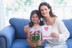 Cute girl offering flowers and card to her mother Stock Images