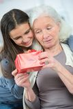 Cute girl offering gift s to grandmother. Cute girl offering a gift s to her grandmother stock photography