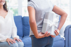 Cute girl offering gift to her mother. In the living room Royalty Free Stock Images
