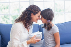 Cute girl offering gift to her mother Stock Image