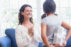 Cute girl offering gift to her mother Stock Images