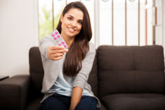 Cute girl offering some medicine. Beautiful young Hispanic woman recommending and handing over some pills to the camera. Focus on pills Stock Photo