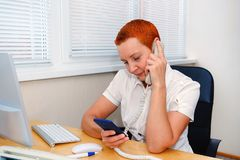 Cute girl office Manager talking on the phone. Smiles in a good mood royalty free stock photography
