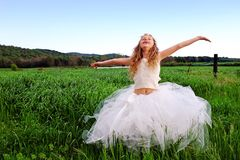 Cute girl with open arms in green grass field. Royalty Free Stock Photos