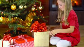 Cute girl open present at christmas time. Near the fireplace stock video