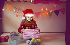 Cute girl opening box with Christmas present stock photos