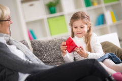 Cute girl opening gift presented by grandmother. With surprise face royalty free stock image