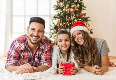 Cute girl opening a magical present on a Christmas morning with her family royalty free stock photo
