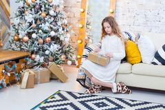 Cute girl opening a present on a Christmas morning.  Stock Photo