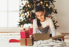 Cute girl opening a present on a Christmas morning. At home Royalty Free Stock Image
