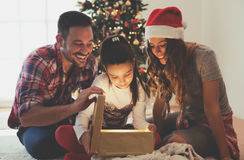 Cute girl opening a present on a Christmas morning with her family Stock Image