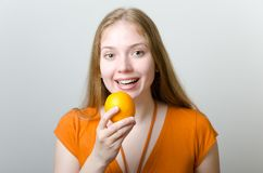 Cute girl with an orange Royalty Free Stock Photos