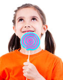 Cute girl in orange t-shirt with colored candy. Royalty Free Stock Photography